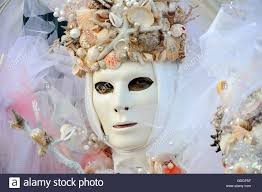 volto mask wearing volto masks at the carnival of venice stock photo