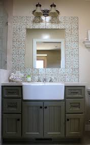 mirror with patterned ceramic tiles a couple of vanity lamps over