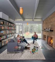 mid century modern library with grey comfy sofa and rustic stone