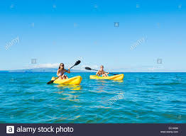 couple kayaking in the ocean on vacation stock photo royalty free