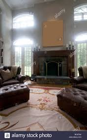 living room in mansion large luxurious living room with leather chairs and a fireplace in