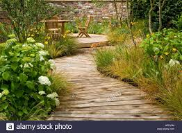boardwalk in garden to decking sitting area with table and chairs