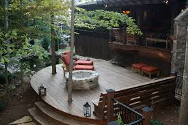curved hardwood deck with firepit stone fireplace bench pond porch