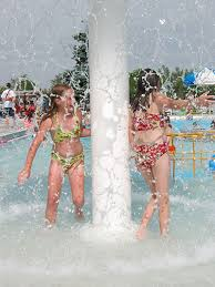 a teen girl applying sun tan lotion while sun bathing on the beach     Orange County Register