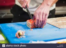 Chef Mat Hand With Knife Cuts Sushi Small Mat On Cooking Board Japanese