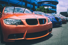 bmw car orange bmw car beside blue bugatti car free stock photo