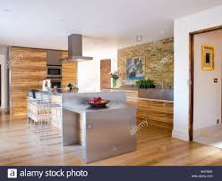 stainless steel island unit in large modern kitchen with wood