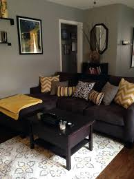 grey walls brown sofa dark brown couch living room artistic sun shape mirror dark brown
