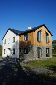passive house larch cladding dressed stone and white render
