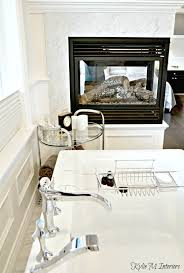gas fireplace in ensuite bathroom with marble surround and free