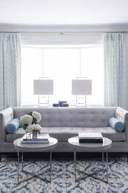 blue and gray living room gray tufted high back sofa with blue bolster pillows transitional