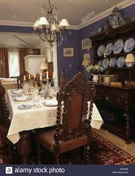 antique jacobean style chairs and oak dresser in blue dining room