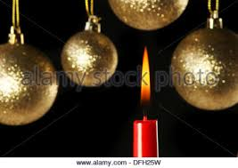candle and and gold baubles in vertical format with