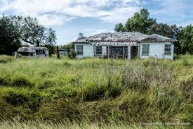 two abandoned farm houses and old ford econoline motor home near