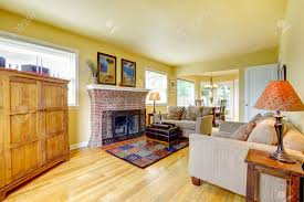 Yellow Fireplace by Yellow Tones Living Room With Hardwood Floor And Brick Background
