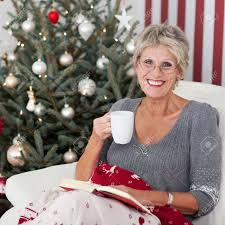 what to get an elderly woman for christmas smiling elderly woman with a cup of tea and a book relaxing in