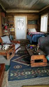 one room cabin living room with twin bed old oak walls with tin