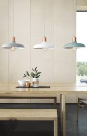 of different shaped pendant lights gathered over a dining table