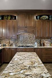 kitchen island stove brown granite countertop tiled backsplash wood cabinet kitchen