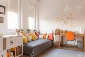 Orange Accessories Yellow And Orange Accessories In Modern Teen Room Stock Photo