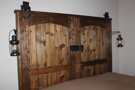 interior brown wooden double sliding barn door hanging on black