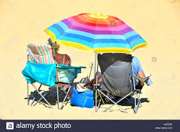 Beach Shade Umbrella Mature Couple Colourful Uk Beach Umbrella Relaxing In Fold Up