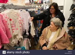 clothing for elderly elderly in wheelchair and carer shopping for baby clothes