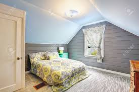 light grey bedroom interior with vaulted ceiling and plank paneled