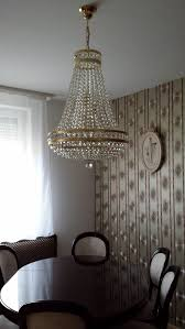 hanging crystal chandelier in the ceiling over dining table add