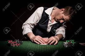 cards on the table a male gambler checks once his cards on the table before placing