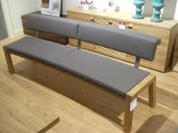 long brown wooden bench with gray seat puff and back placed on the