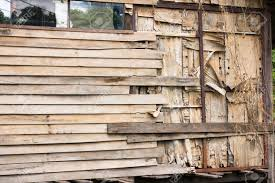 wooden slat wall of an old house are peeling off due to lack