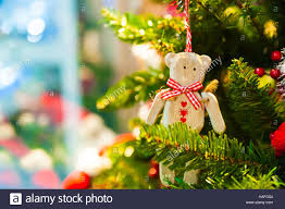 old wooden toy bear with a red bow ribbon hanging on christmas