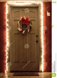 Red And White Christmas Lights by Christmas Lights And Wreath On Front Door At Night Stock Photo