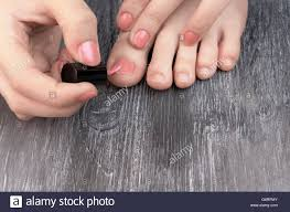 teen applying nail polish to hands and feet fingers stock photo