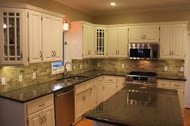 black granite countertops with tile backsplash and dining table
