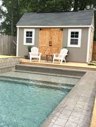 pool house front is sliding glass doors with pergola built off of