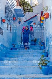 blue city morocco woman in blue djellaba and child in blue city morocco stock photo