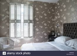 osbourne little mettalic floral print wallpaper in bedroom with osbourne little mettalic floral print wallpaper in bedroom with plantation shutters and chrome anglepoise lamps