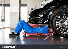 car service mechanic blue uniform lying down working stock photo 406431103
