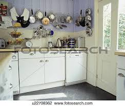 stock photo of stainless steel pans on wall above electrical