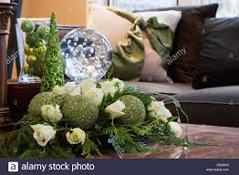 close up of christmas decorations green baubles with white roses