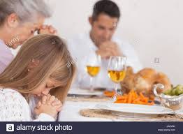 saying grace with family before thanksgiving dinner