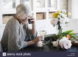 woman drinking wine arranging flowers talking on telephone stock