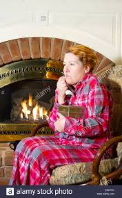mature woman dressed in flannel pajamas sitting in a chair in