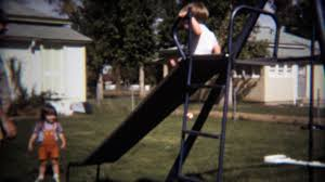1971 baby boy and sister sliding on backyard playground jungle
