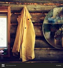 raincoat hanging next to a mirror on the wall of a rustic log