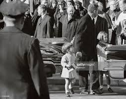 young john f kennedy jr being escorted at gravesite of jfk