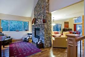 traditional living room with stone fireplace by sheila hall