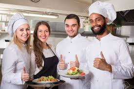 equipe cuisine positive waitress and cooking team at professional kitchen in